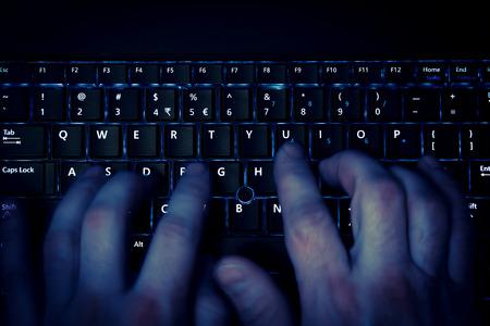 teclado de computadora: manos escribiendo en el teclado en luz azul con el desenfoque de movimiento