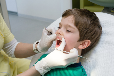 little boy having his teeth checked by dentist Stock Photo