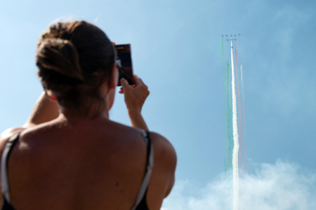 spectator: SLIAC, SLOVAKIA - AUGUST 29: Spectator takes picture of Italian aerobatic team Frecce Tricolori in action at SIAF airshow in Sliac, Slovakia on August 29, 2015