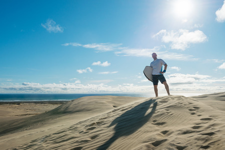 ninety: young man posing with board at Te Paki sand dunes, New Zealand