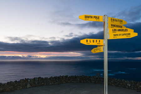 km: Sign with distances in km and nm from Cape Reinga, New Zealand at dusk