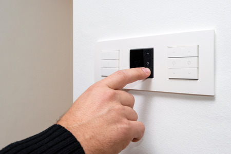 dimmer: Closeup shot of mans hand controlling multipurpose switch