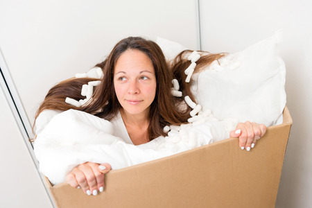 Young woman in a box with packing material