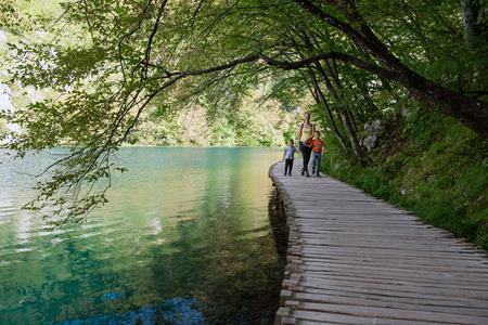 Young wife with two kinds on tourist path in Plitvice lakes National Park, Croatia