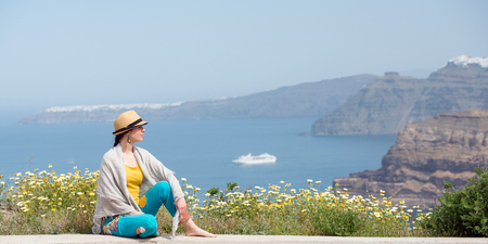 Young woman on the meadow full of flowers, Santorini, Greece Stock Photo
