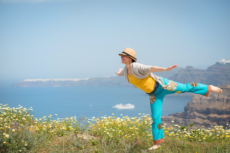Young woman having fun on the meadow full of flowers during vacation, Santorini, Greece