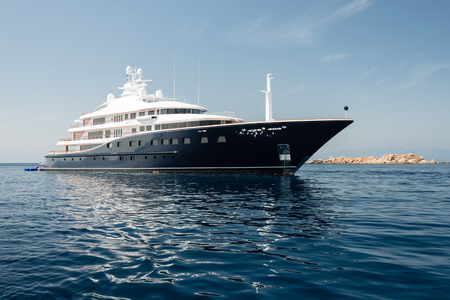 Large luxury motor yacht anchored near rocky island