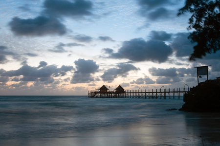 Wooden pier and thatched roofs on a tropical beach at sunrise, Zanzibar island