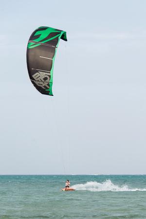 JAMBIANI, ZANZIBAR - DEC 22, 2017: Man riding a kiteboard in a high speed on Jambiani beach, Zanzibar