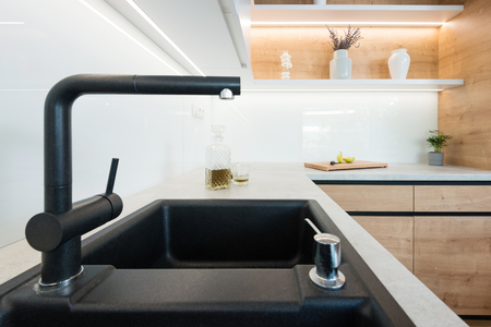 Detail of black wash basin with faucet in modern kitchen