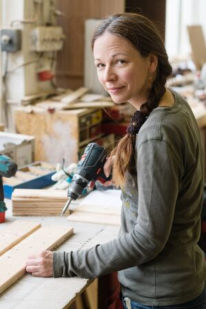 Young woman using a electric screwdriver on a piece of wood at workshop