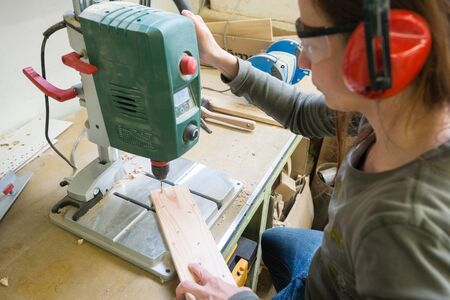 Young woman with drill perforating wood plank at workshop