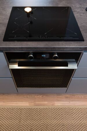 Electric stove with induction cooktop in contemporary kitchen Banco de Imagens - 132448546
