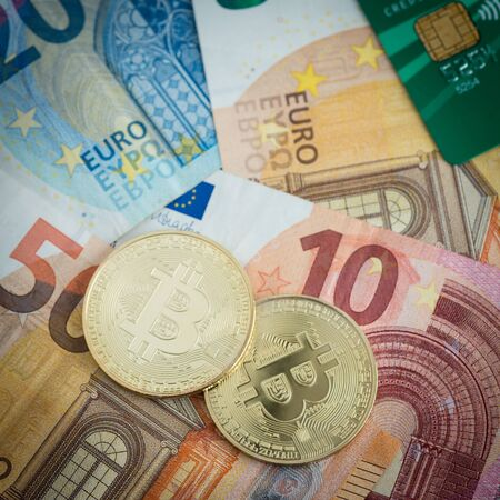 Golden bitcoins with euro notes and credit card in background, new currency, finance concept