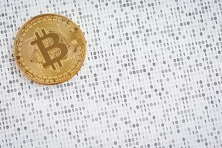 Crypto currency coin - golden Bitcoin on black and white binary 1 and 0 background 스톡 콘텐츠
