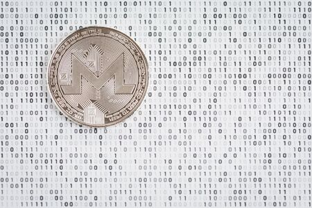 Cryptocurrency coin - silver Monero on black and white binary 1 and background Stock Photo