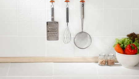 Kitchen cooking utensils on hook against tile wall photo