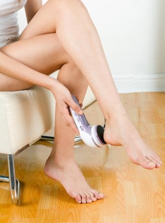 A woman polishing her foot with polish machine Stock Photo - 16658475