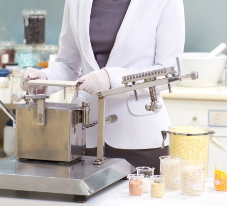 A pharmacist preparing medication with packaging capsule machine photo