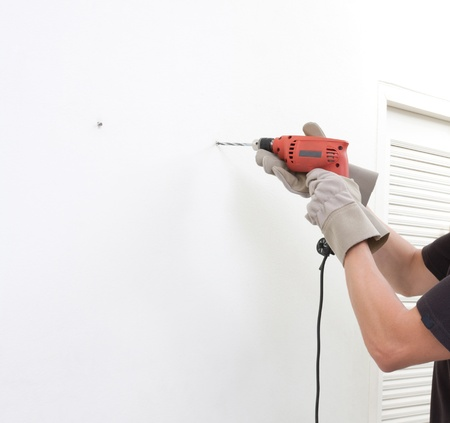 screw: a man using an electric screwdriver with empty space on the wall