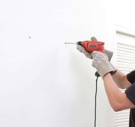 tornillos: un hombre usando un destornillador el�ctrico con el espacio vac�o en la pared Foto de archivo