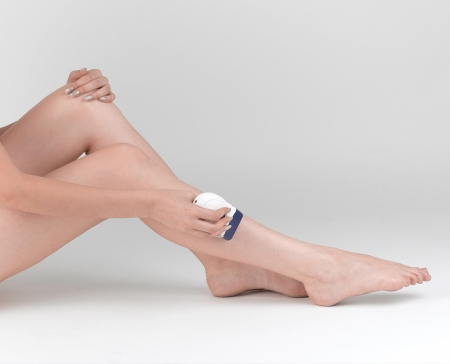 shorten: Woman trimming her leg with electric trimmer Stock Photo