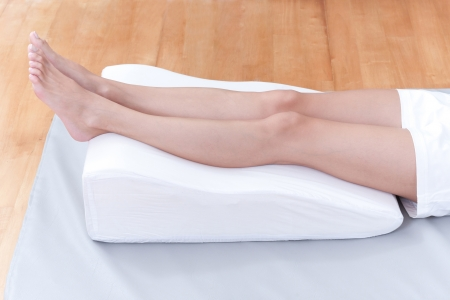 varicose veins:  A womans legs lay down on a pillow for relaxing and preventing varicose vein