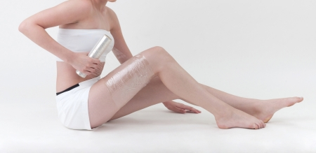 body expression: A woman wrapping her leg with plastic wrapper Stock Photo