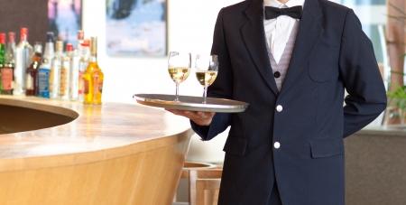 trays: Un camarero con una bandeja con copas de vino blanco para servir