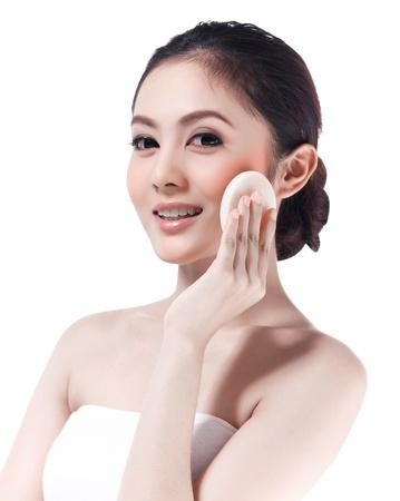 Muchacha asiática joven compone su cara