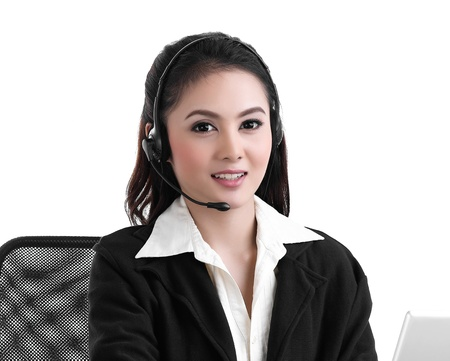 A pretty call center woman in headset talking with customer