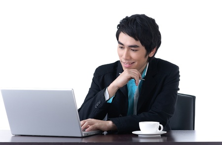 A happy young business man working with laptop photo