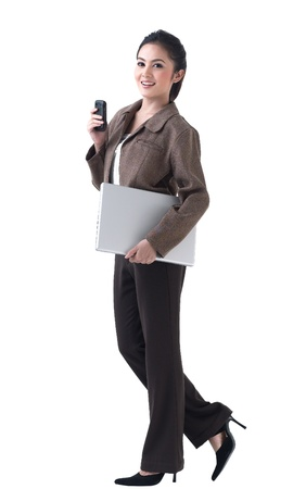 A beautiful asian business woman walking with laptop and on the phone photo