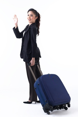 A happy woman pulling her luggage and waving her hand to good bye her family photo