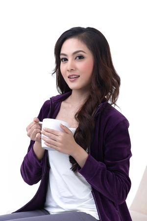 A beautiful young woman sitting and holding a cup of coffee photo