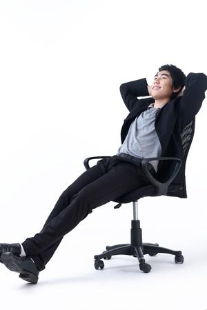 obrero trabajando: Relajado hombre de negocios joven sentado en la silla Foto de archivo