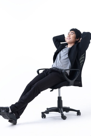 Relaxed young business man sitting on the chair photo