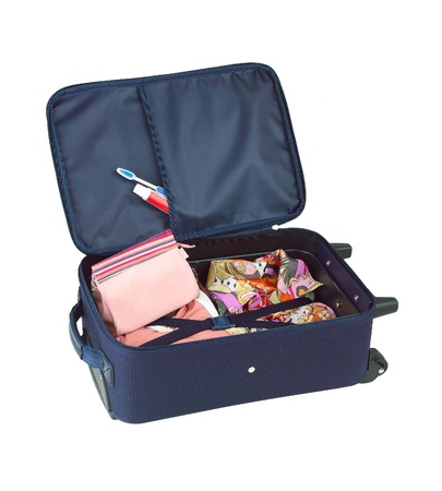 An opened suitcase packed with colorful cloth and cosmetic bag photo