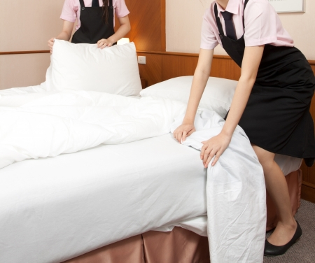 women maid making bed in hotel room