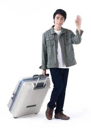 lucky man: A young traveler man waving hand and pulling his luggage, come back from taken vacation