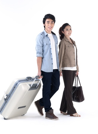 Young couple walking and pulling a luggage photo