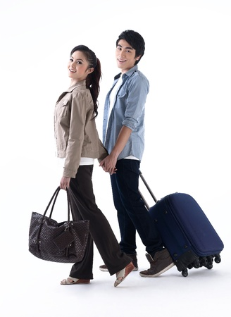 carry bags: Young couple walking and pulling a luggage Stock Photo