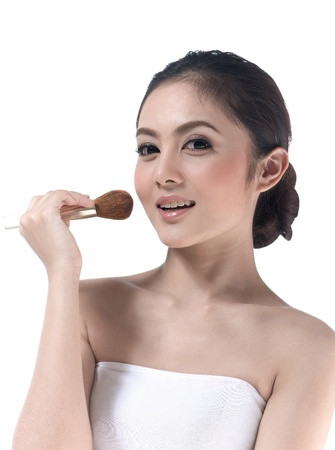 A pretty young woman makeup her face with brush photo
