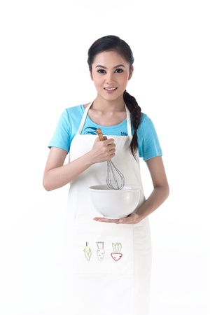 stirring: A happy housewife holding a bowl and whisk