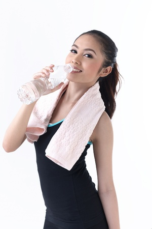 Young woman drinking water after exercise photo