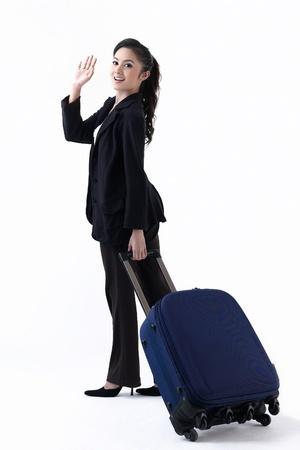 femme valise: Une femme heureuse en tirant ses bagages et en agitant sa main pour revoir sa famille Banque d'images