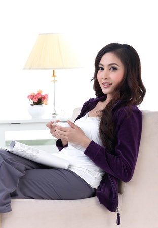 A young attractive woman sitting in a living room with a cup of coffee photo