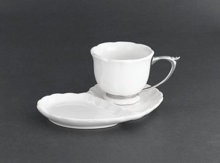 A cup of coffee or tea with causer designed which have a space to put some snack on it photo