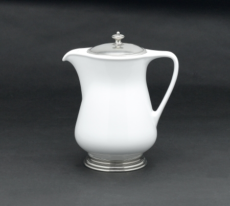 pewter mug: A porcelain pitcher for milk , tea or coffee decorated by pewter