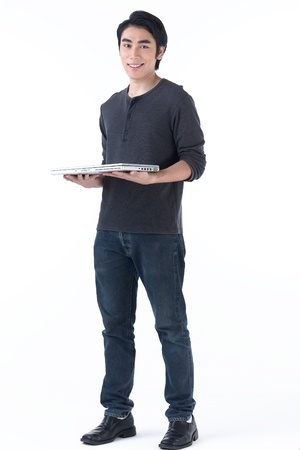 A happy asian man standing and hold laptop computer in his hands photo